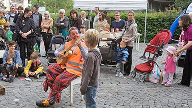 Eine Clownin spielt Gitarre auf einem Platz in der Altstadt, umringt von Kindern.