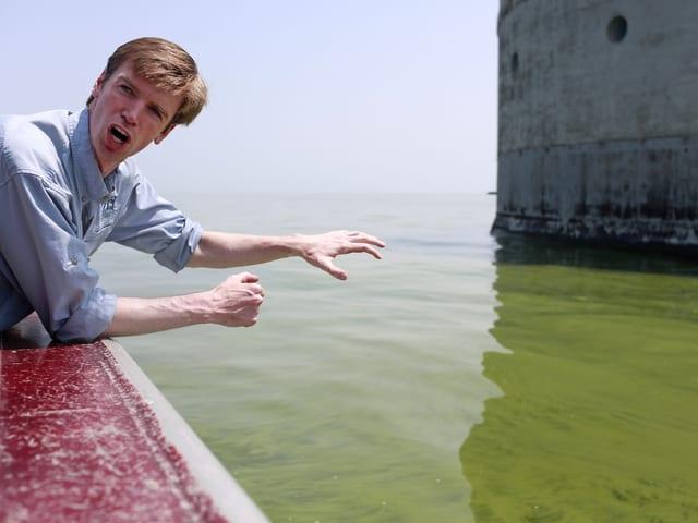Ein Mann beugt sich über eine Mauer, dahinter ist grünes Wasser zu sehen