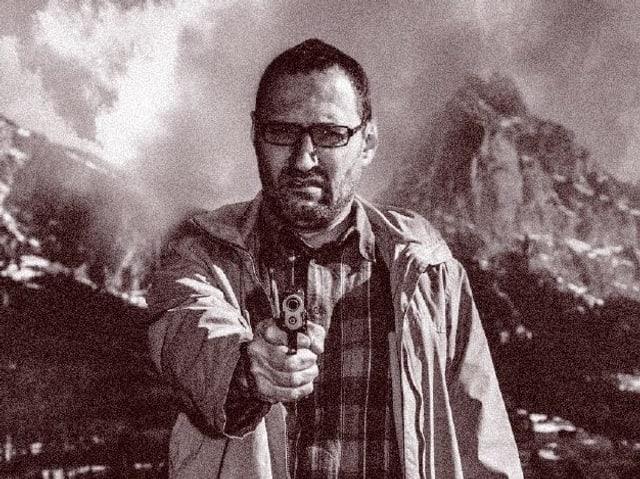 Ein Mann zielt mit einer Pistole auf den Betrachter.
