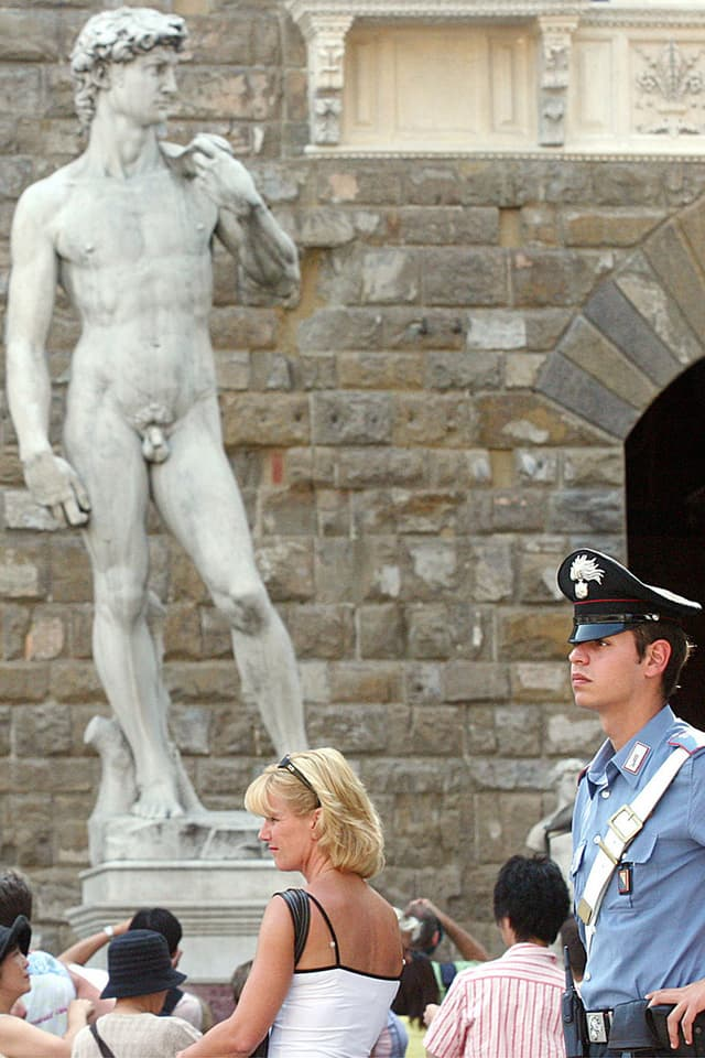 David von Michelangelo in Florenz, davor Touristinnen und ein Polizist.