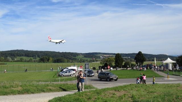 Landendes Flugzeug mit Parklplatz im Vordergrund