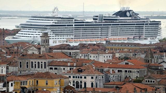 Ein Kreuzfahrtschiff im Hintergrund überragt die Stadtsilhouette von Venedig