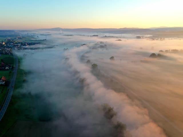Morgennebel breitet sich im Tal aus.