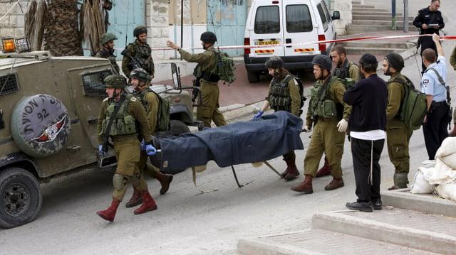 Israelische Soldaten tragen die Leiche des Palästinensers weg