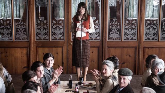 Eine Frau am Mikrofon spricht in einem Restaurant zu anderen Frauen.