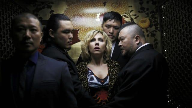 Lucy umringt von Männern.