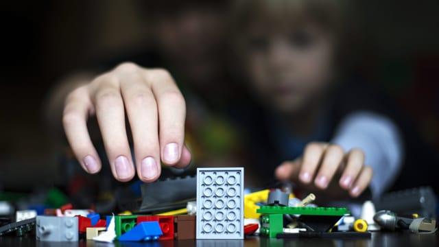 Eine Erwachsenen- und eine Kinderhand greifen nach Legobauklötzen.