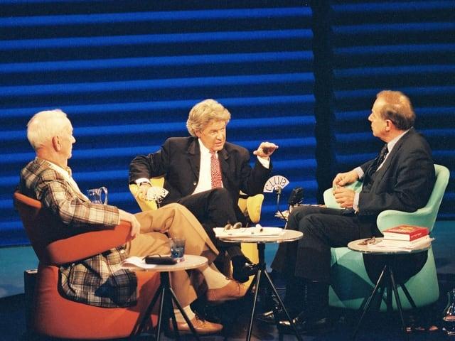 Drei Männer sitzen auf bunten Sesseln und diskutieren.