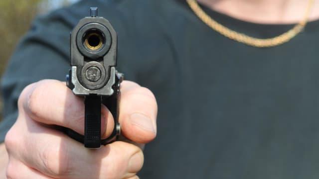 Pistole in der Hand eines Mannes (Symbolbild)