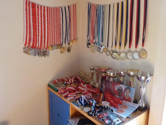 Medaillen an der Wand und auf dem Schrank.