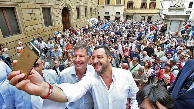 Salvini macht ein Selfie, neben ihm steht ein Mann, beide grinsen in die Kamera, dahinter viele Leute.