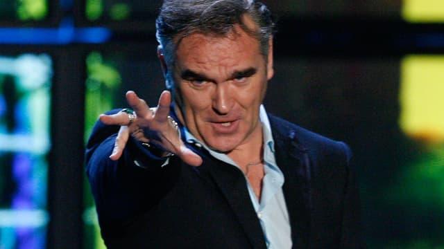 Morrissey singend, mit ausgestreckter Hand zur Kamera