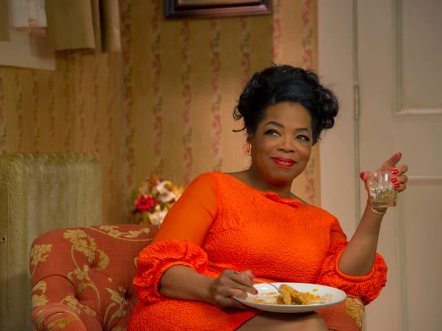 Filmszene mit Oprah Wonfrey auf einem Wohnzimmersessel.
