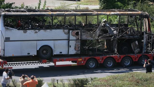 Ein ausgebrannter Bus auf einem LKW-Anhänger.
