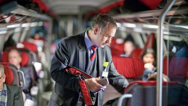 Ein Kondukteur bei der Arbeit in einem Zug.