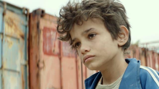 Ein kleiner Junge blickt wütend und traurig in die Kamera.
