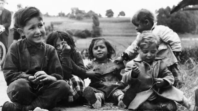 Kinder sitzen am Boden, historische Aufnahme