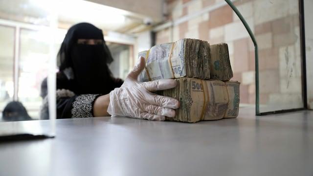 Eine verschleierte Frau bündelt Banknoten.