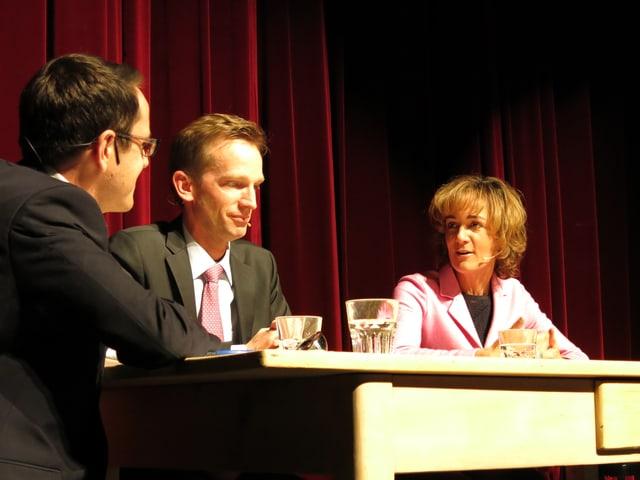 Thomas Pressmann, Alexandre Schmidt und Ursula Wyss am Tisch auf dem Podium