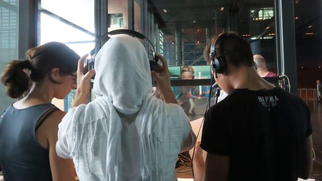 zwei Jugendliche setzen sich Kopfhörer auf.