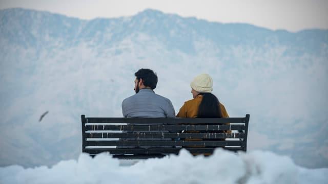 Ein Paar sitzt im Winter auf einer Bank mit schneeweissen Bergen im Hintergrund