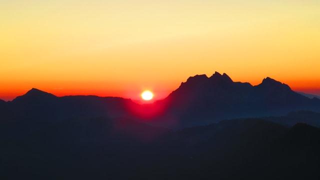 Die Sonne taucht um 05.30 Uhr links neben dem Pilatus auf, der Himmel leuchtet am Horizont rot und orange. Die Sonnenscheibe steht knapp über der Bergkette.