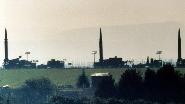 Hinter einer Wiese ragen drei schmale Raketen in die Höhe.