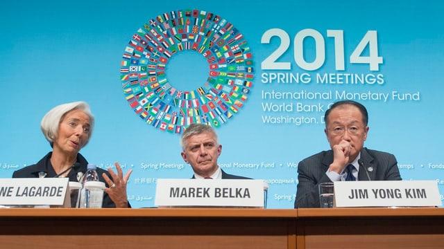 Eine Frau und zwei Männer sitzen vor Mikrofonen.