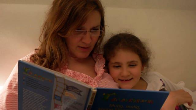 Eine Mutter liest zusammen mit ihrer Tochter ein Buch.