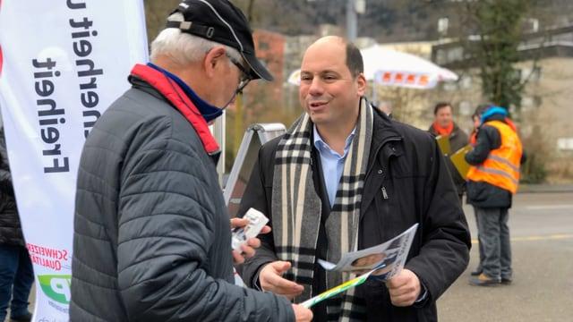 SVP-Nationalrat und Präsident der SVP Stadt Zürich verteilt Flyer an einen älteren Passanten.