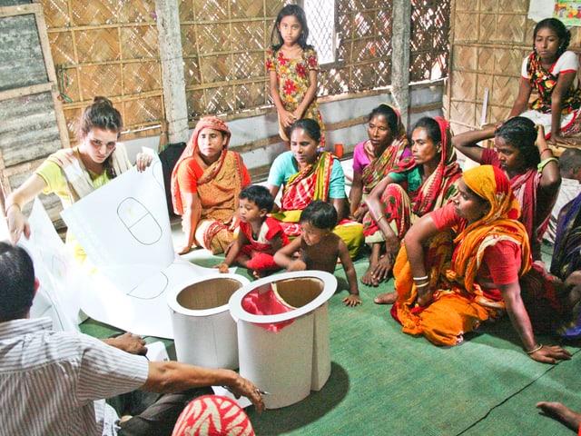 Eine weisse Frau zeigt bunt gekleideten Frauen aus Bangladaseh die Baupläne einer Toilette.