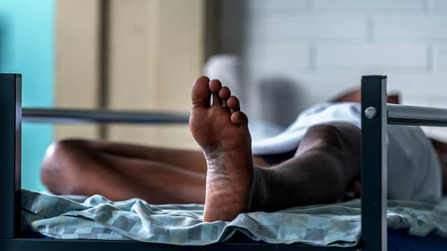 Auf einem Bett liegende Person in einem Empfangszentrum