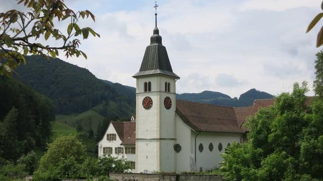 Kirche, dahinter Wald und Hügel.