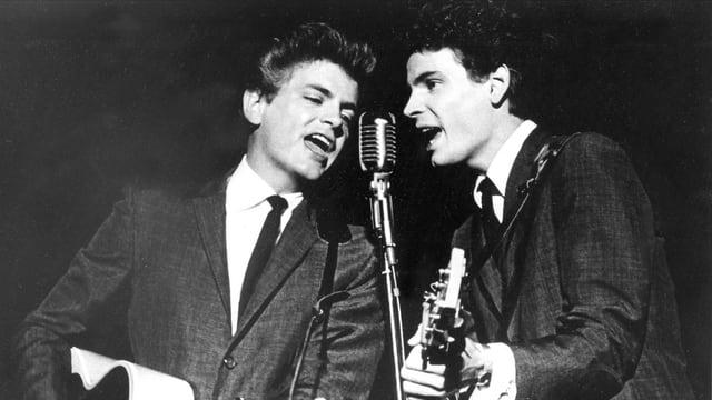 Zwei junge Männer mit Gitarre singen in ein Mikrofon