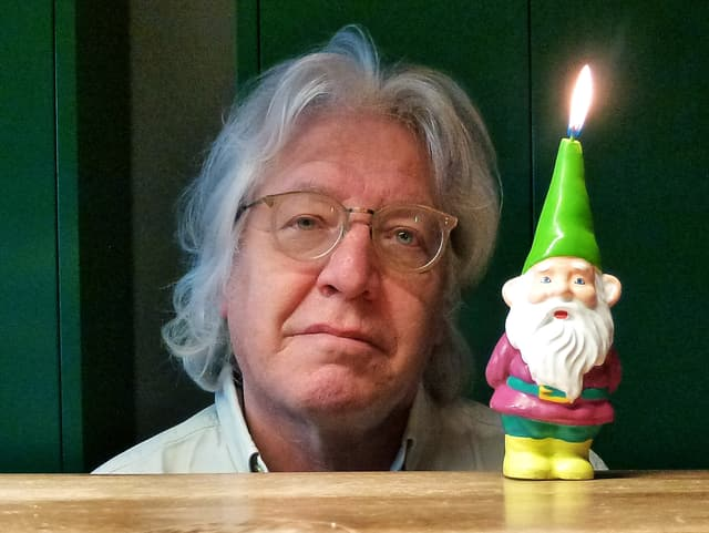 Das Porträt eines Mannes, dessen Gesicht neben einer Kerze in Form eines Zwerges zu sehen ist.