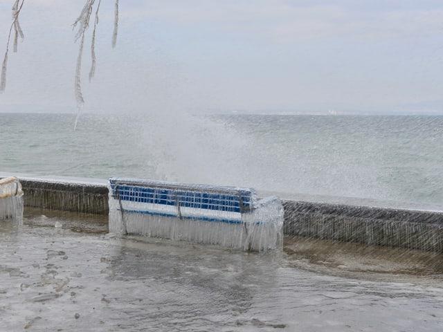 Uferpromenade mit Sitzbank, alles dick vereist. Düsteres Wetter mit Wellengang auf dem See.