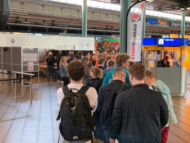 Eine Menschenschlange steht vor dem Wahllokal am Flughafen Amsterdam Schiphol.