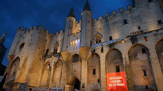 """Die Fassade des Papstpalastes in Avignon, beleuchtet bei Nacht. Im Vordergrund Demonstranten und ein Banner mit der Aufschrift: «Refusons l'accord du 22 mars"""""""