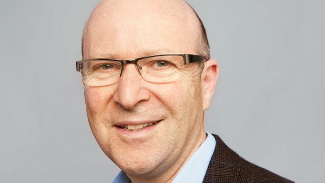 Das Bild zeigt einen mittelalten Mann mit Brille, der lächelt.
