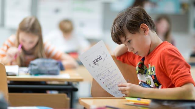 Junge mit orangem Pullover - hält ein Blatt in der Hand