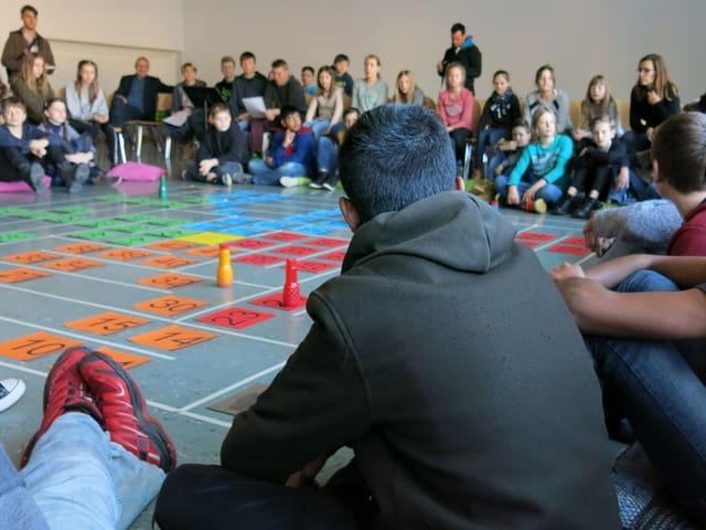 Kinder sitzen am Boden vor einem grossen Spiel mit Würfel und Figuren.