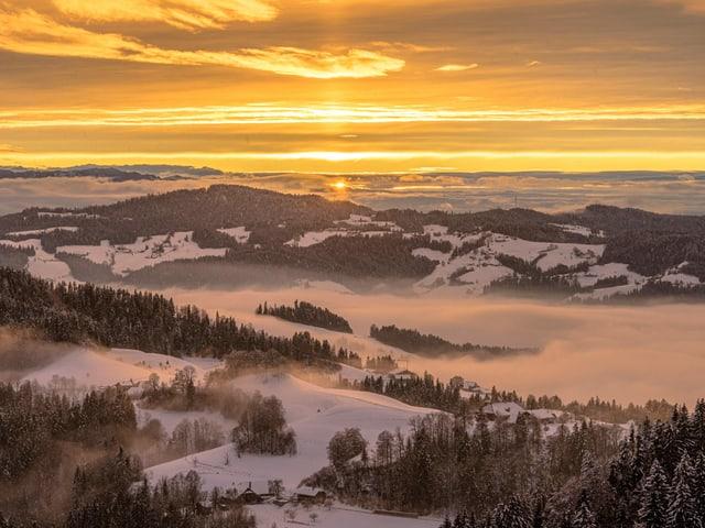 Sonnenuntergang hinter einer verschneiten Hügellandschaft