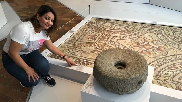 Sherin Abdulhannan kniet vor einer Handmühle im Museum zu Allerheiligen