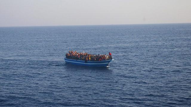 Flüchtlingsboot mit Menschen im Meer