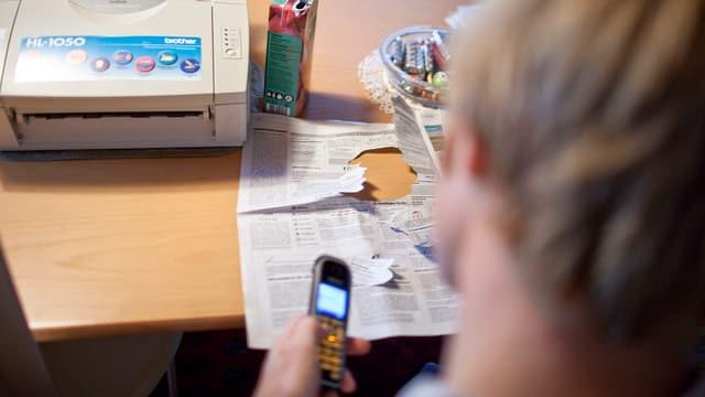 Junger Mann auf Jobsuche telefoniert mit einem möglichen Arbeitgeber.