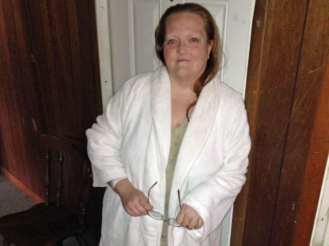 Angie steht im Bademantel vor ihrer Wohnung. Sie hat rötliche lange Haare und hält ihre Brille in den Händen.