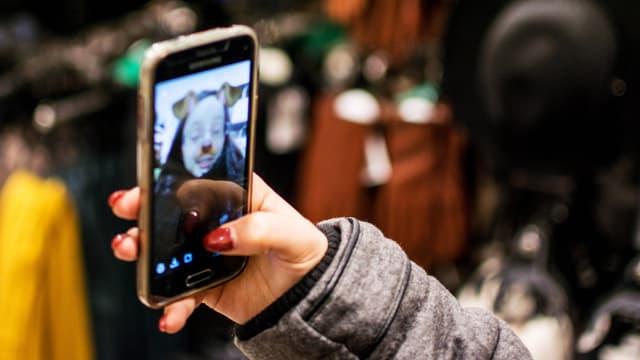 Eine junge Frau blickt auf ein Smartphone mit FIlter-Selfie.
