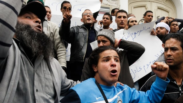 Männer mit Transparenten demonstrieren.