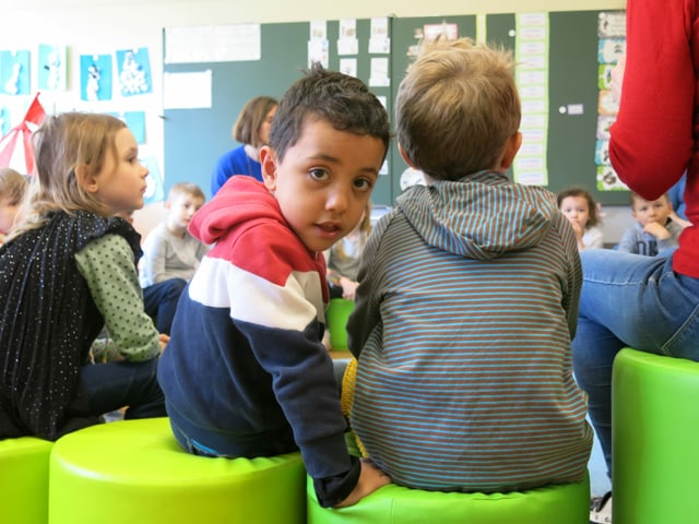 Kinder im Kindergarten, ein Junge schaut in die Kamera