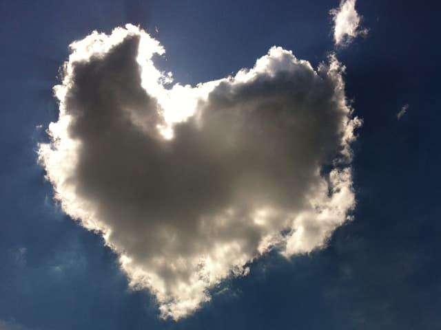 Stahlblauer Himmel mit herzförmiger Wolke. Diese Wolke hat sich vor die Sonne geschoben.